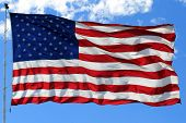pic of waving american flag  - An American flag waves in the breeze with blue sky in the background - JPG