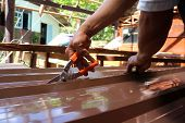 Workers use scissors to cut the metal sheet for roofing a local house.