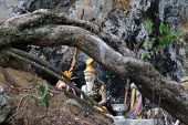 The statue of hermit near the limestone cave in Thailand.
