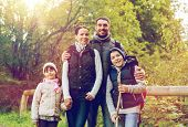 hike, travel, tourism and people concept - happy family walking with backpacks in woods poster