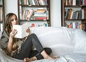 Girl Reading Book On Sofa poster