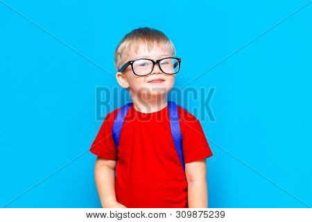 poster of Happy Smiling Boy In Red T-shirt In Glasses Is Going To School For The First Time. Child With School