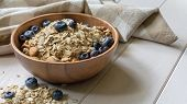 Oatmeal With Blueberries, Almond And Walnuts In A Wooden Bowl On A Black Wooden Table poster