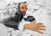 stock photo of adversity humor  - Businessman sinking in heap of documents and asking for help - JPG