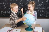 Geography Lesson: A Boy And A Girl Are Sitting On A Desk And Studying The Globe On The Background Of poster