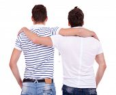 pic of gay couple  - back view of two friends  standing embraced and looking at something on white background - JPG