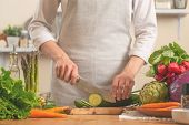 The Chef Cuts Cucumber On A Light Background. A Concept Of Losing Healthy And Wholesome Food, Detox, poster