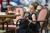 Cute Little Girl In A Beautiful Black Evening Dress Dining At A Table In A Summer Cafe.cute Little G poster