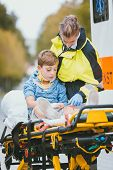 Emergency doctor giving oxygen to accident victim, a child poster