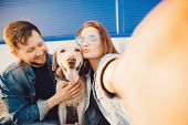 Happy Couple Making Selfie Photo With Dog Labrador Retriever Smiling. Concept Young Family poster