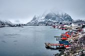 Reine fishing village on Lofoten islands with red rorbu houses in winter with snow. Lofoten islands, poster