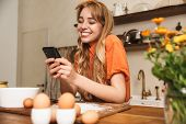 Picture of a happy cheerful smiling young blonde girl chef cooking at the kitchen using mobile phone poster