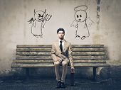 stock photo of sitting a bench  - Businessman sitting on a bench with an angel and a devil on his sides - JPG