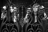 Sad young women clinging on an iron fence