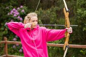 stock photo of archery  - Concentrating blonde practicing archery at the range - JPG