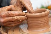 stock photo of molding clay  - craftsman works in clay dishes outside handmade - JPG