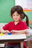 stock photo of molding clay  - Little preschool boy molding clay at desk in classroom - JPG