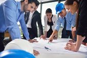 stock photo of blueprints  - business people group on meeting and presentation  in bright modern office with construction engineer architect and worker looking building model and blueprint planbleprint plans - JPG