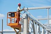 stock photo of assemblage  - worker in uniform and safety protective equipment at metal construction frames installation and assemblage - JPG