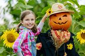 Scarecrow and happy girl  in the garden - Autumn harvests, Thanksgiving vegetable, Halloween