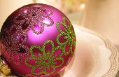picture of mustering  - closeup of a pink shiny christmas tree ball with decorative green and glittering pattern in a porcelain plate - JPG