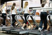 young women in the gym center, running on treadmill