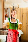 foto of stein  - Young woman as queen in Traditional Bavarian Tracht in restaurant or pub with steins and beer - JPG