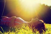 stock photo of grass  - Young pretty woman lying on the grass at summer sunset - JPG