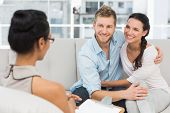 image of counseling  - Smiling couple reconciling at therapy session in therapists office - JPG