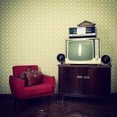 Vintage room with wallpaper, old fashioned armchair, retro tv, bag, clocks, radio player and loudspe