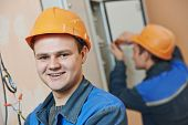 Happy young adult electrician builder engineer in front of his co-worker screwing equipment in fuseb