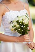 Close-up mid section of a young beautiful bride with bouquet in the park