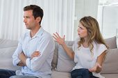 Unhappy couple having an argument in living room at home