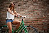 Portrait of young woman riding bicycle against brick wall