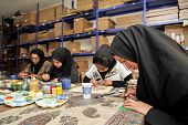 ESFAHAN, IRAN - DECEMBER 01, 2007:  Muslim women artists in black headscarfs paint traditional Persi