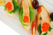 healthy appetizer : sandwich with sea salmon and red caviar, olives, tomato and lemon on white china