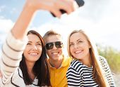 summer, holidays, technology, vacation and happiness concept - group of friends taking picture with