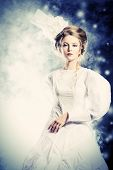 stock photo of snow queen  - Portrait of a beautiful fashion model in the refined white dress and elegant hat - JPG