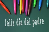 feliz dia del padre, happy fathers day written in spanish in a chalkboard, and some felt-tip pens of