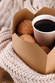 Hot coffee and cookies in box on knitted scarf  close-up