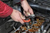 stock photo of overhauling  - Car mechanic replacing ignition coil on gasoline engine - JPG