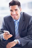 Happy businessman sitting on sofa sending a text in the office