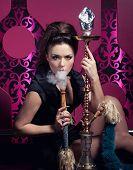 stock photo of hookah  - Beautiful woman smoking hookah in nightclub - JPG