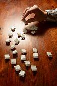 stock photo of scrabble  - Female hands typesetting white keys on wooden background  - JPG