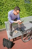 picture of work bench  - Young business man working with electronic tablet while having a lunch break - JPG