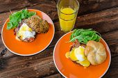 stock photo of benediction  - English muffin with bacon egg benedict with hollandaise sauce and arugula salad fresh orange juice - JPG