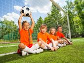 Постер, плакат: Children sit together on field with football
