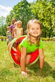 stock photo of crawling  - Group of children play with tube on the lawn with nice Caucasian girl crawling out of pipe with smile and her friends standing in the line - JPG
