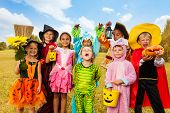stock photo of halloween  - Happy excited kids in Halloween costumes stand close  on green grass of the field - JPG
