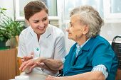 stock photo of nursing  - Nurse assists an elderly woman with skin care and hygiene measures at home - JPG